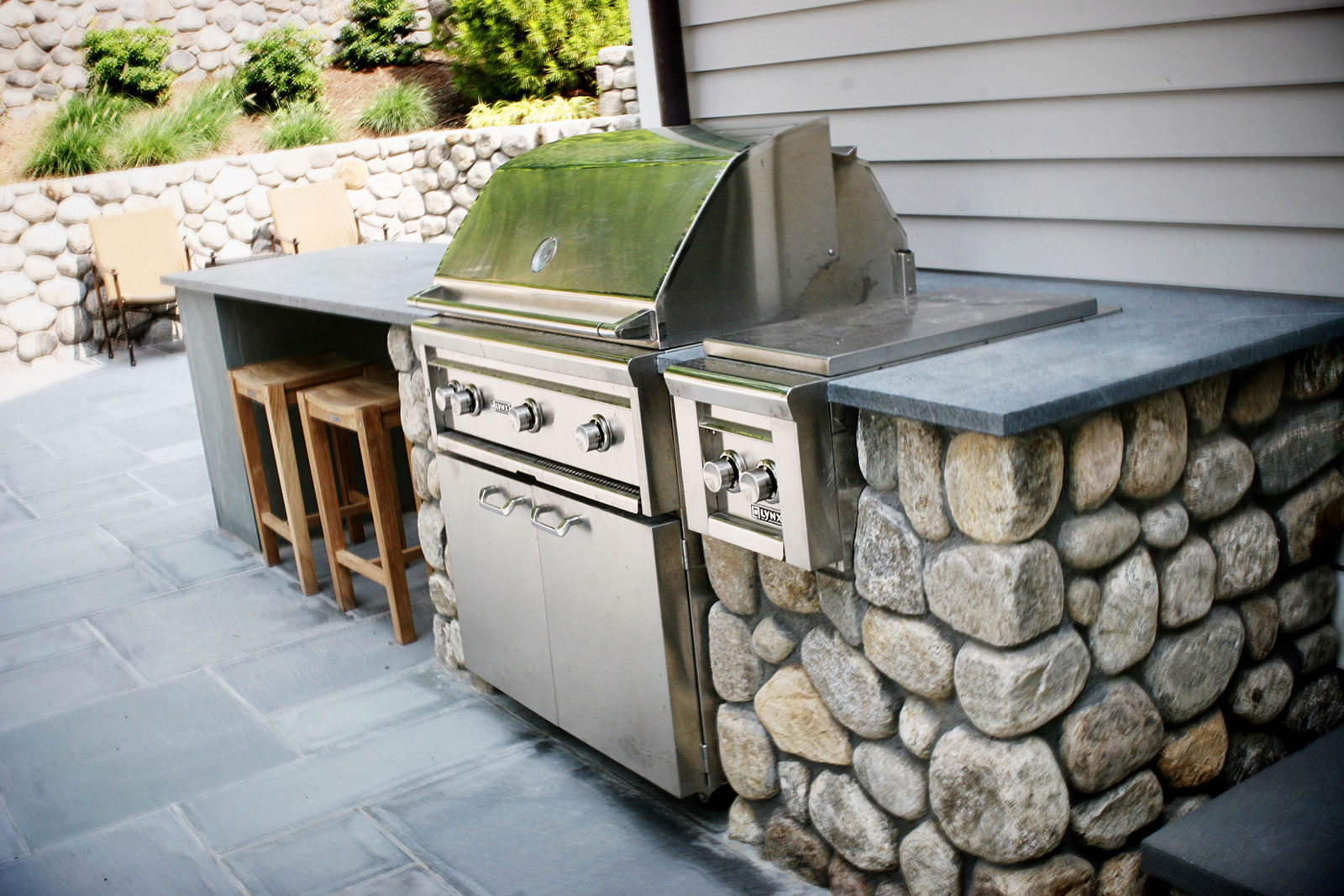 Round Connecticut fieldstone outdoor kitchen with soapstone countertop